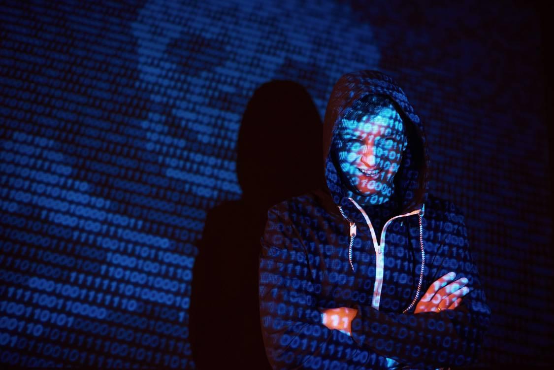 Unrecognizable hooded male hacker